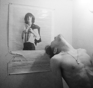 Robert-Mapplethorpe-in-front-of-his-cover-for-Patti-Smith's-Horses-c.-1975